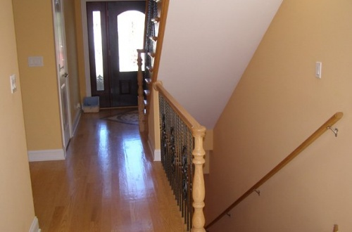 b_breathtaking entry with oak stairs and wrought iron spindles bot up to the second level and down to the lower level
